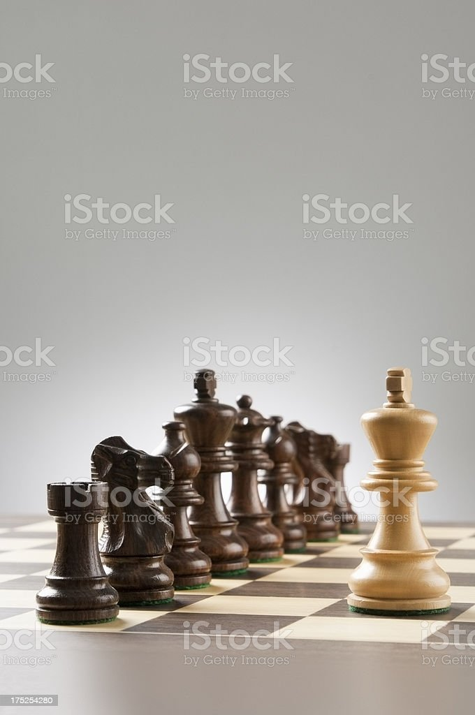 The king chess piece stands surrounded by opposing side stock photo