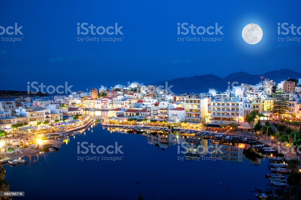 The lake Voulismeni in Agios Nikolaos at night with fullmoon, a picturesque coastal town with colorful buildings around the port in the eastern part of the island Crete, Greece stock photo