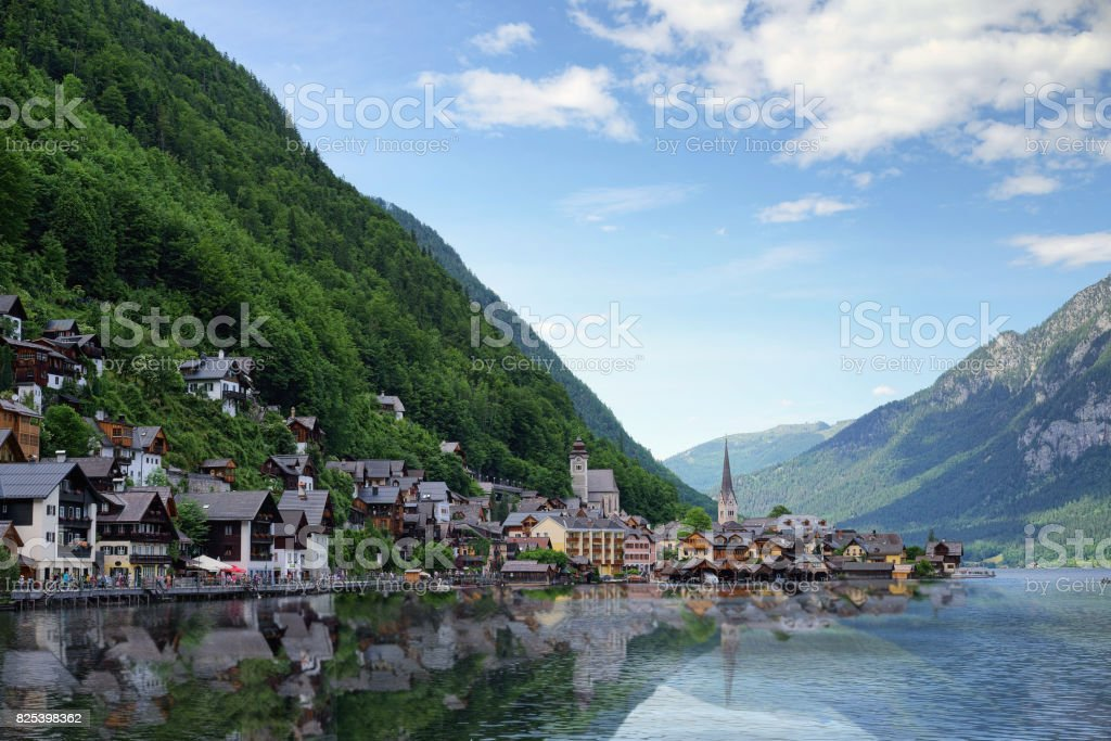 The landscape image of Hallstatt city during the sunny morning from the pier with the water reflection of small village in the Austria Alps stock photo