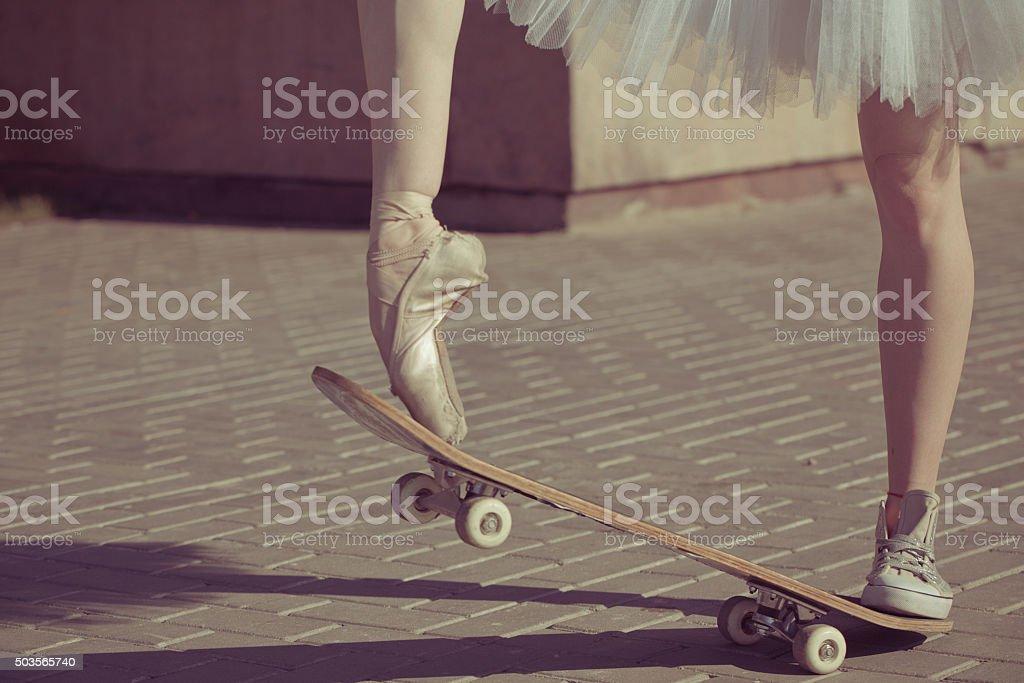 The legs of a ballerina on a skateboard. stock photo