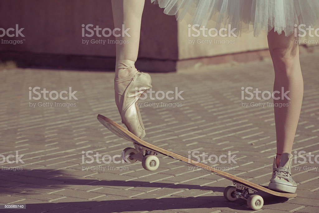 The legs of a ballerina on a skateboard. stock photo