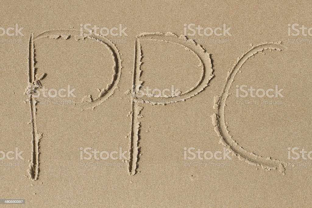 The letters PPC drawn in sand royalty-free stock photo