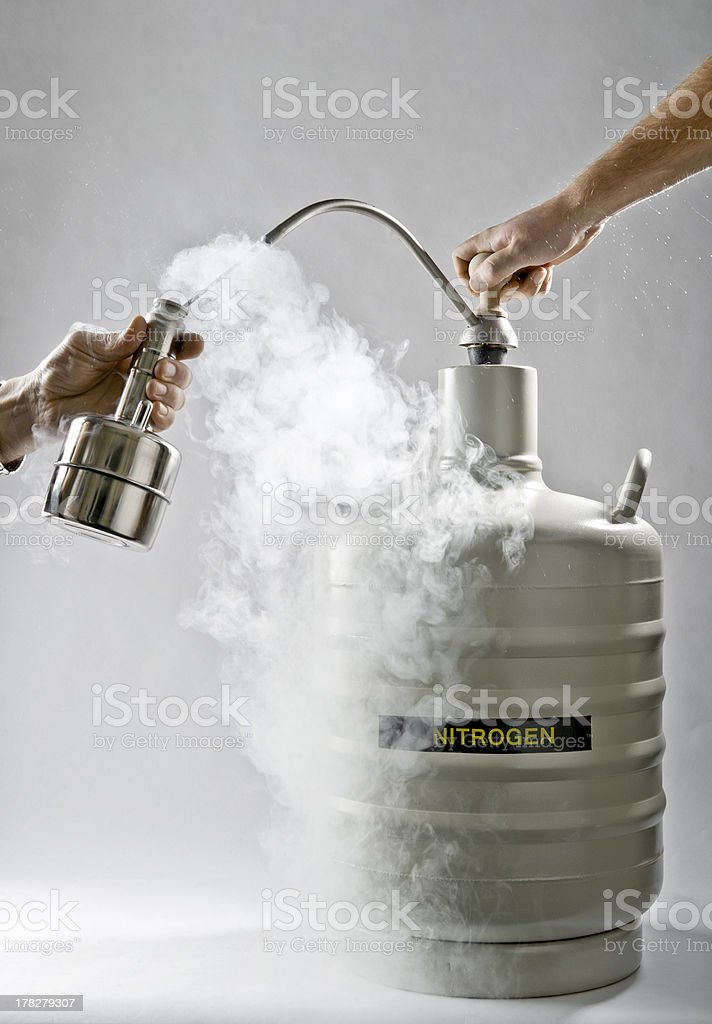 The liquid nitrogen pour from big cask into small royalty-free stock photo