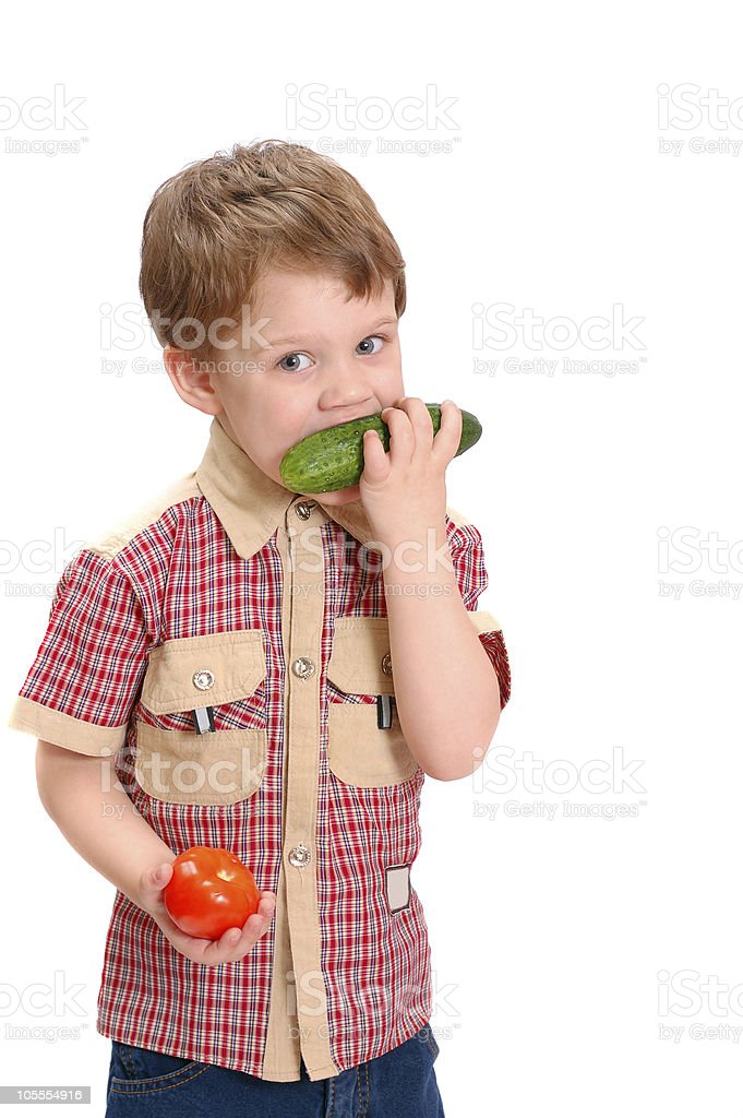 The little boy eats a cucumber isolated on white background royalty-free stock photo