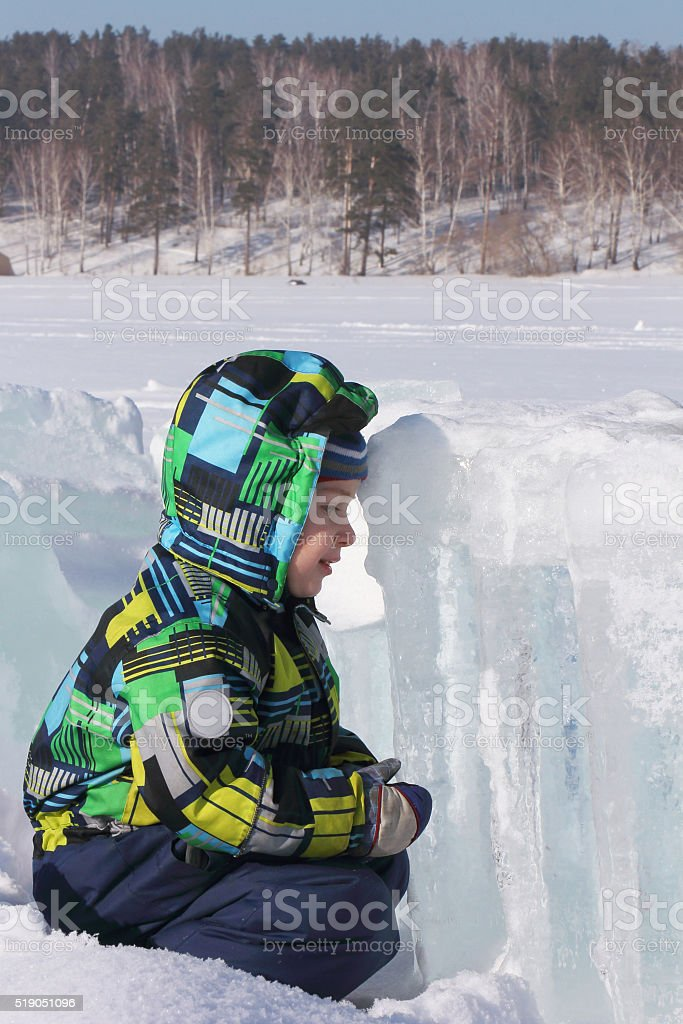 The little boy  sitting opposite to an ice block stock photo