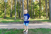 The little boy stand on the stump
