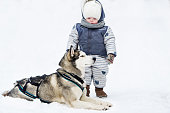 The little girl and dog play in snow.