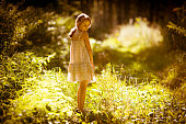 The little girl is in a forest
