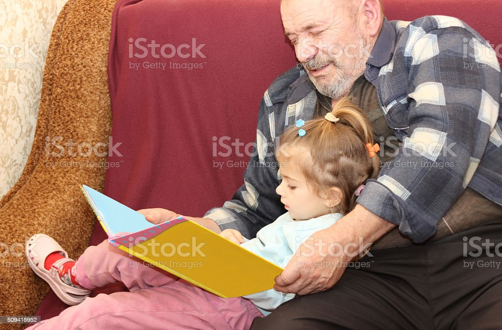 the little girl with the grandfather read the book stock photo