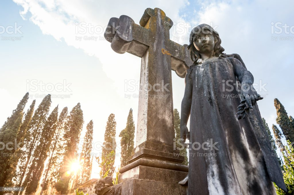 The little girl's statue premature dead, close to the stone cross stock photo