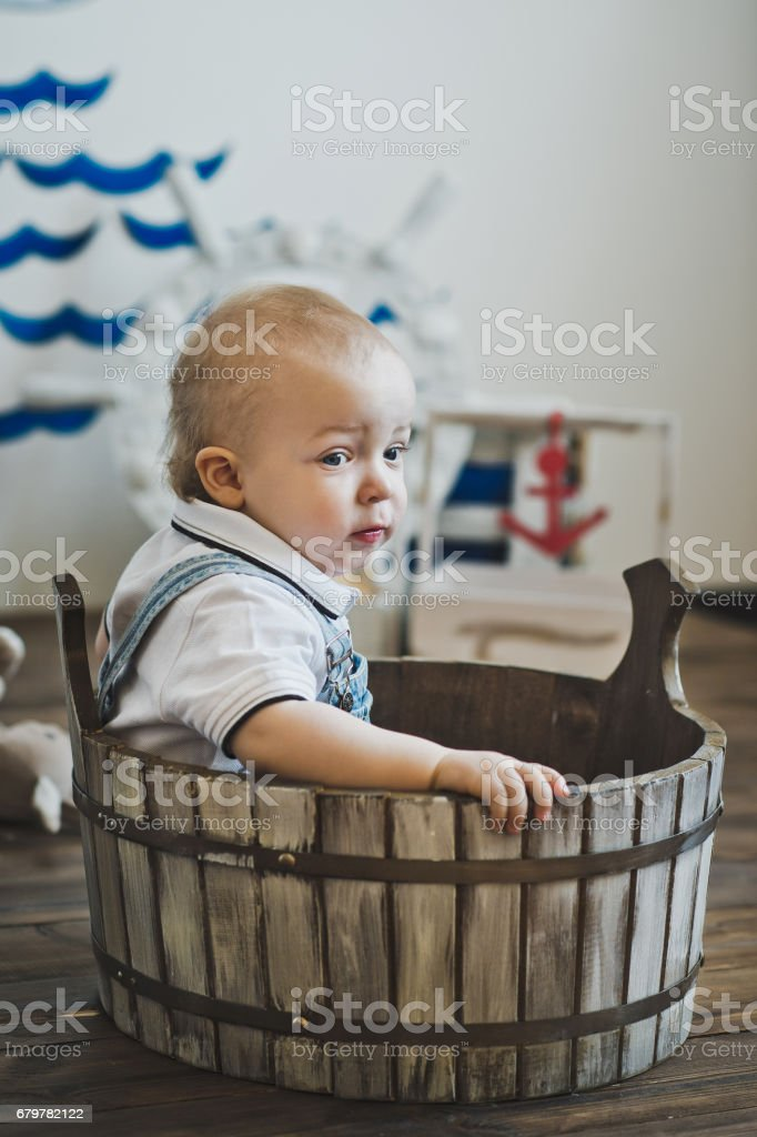 The little one-year-old child is seated in a wooden basin 5532. stock photo