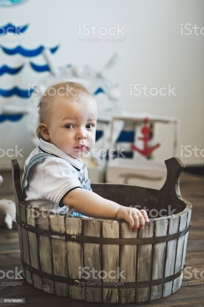 The little one-year-old child is seated in a wooden basin 5533. stock photo