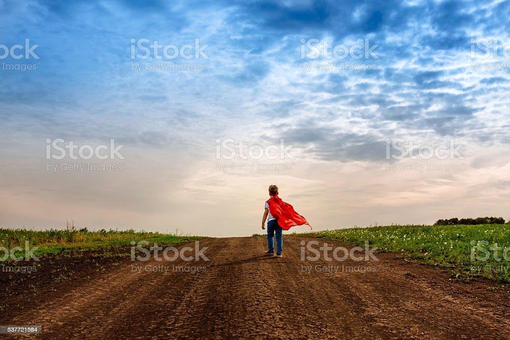 the little preschool boy, plays the superhero outdoors stock photo