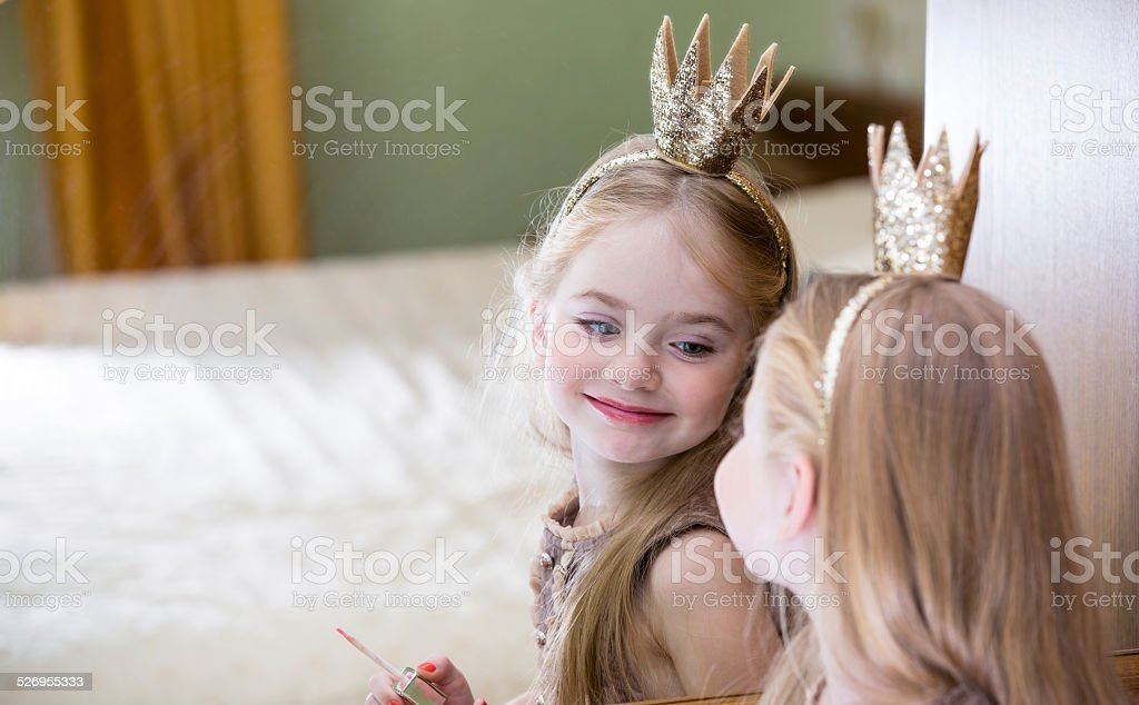 The little princess looks in the mirror stock photo