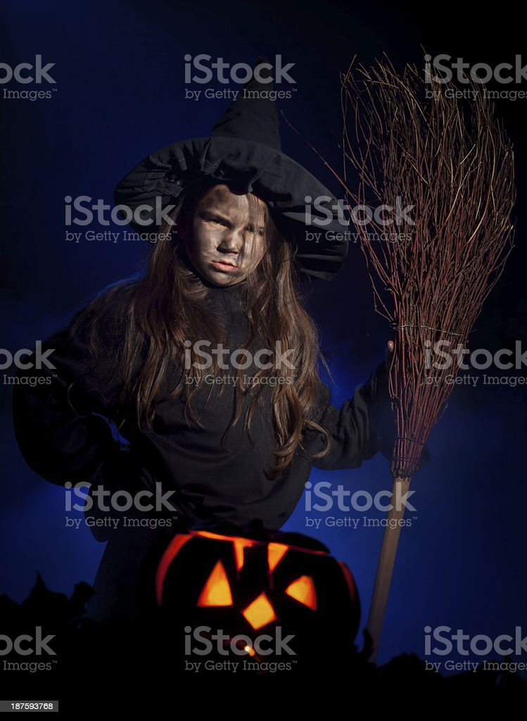 The little witch with halloween pumpkin stock photo