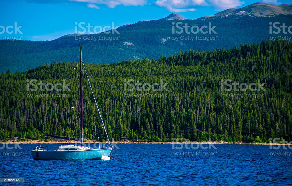 The Lonely Sail Boat on Twin Lakes in the Mountains stock photo