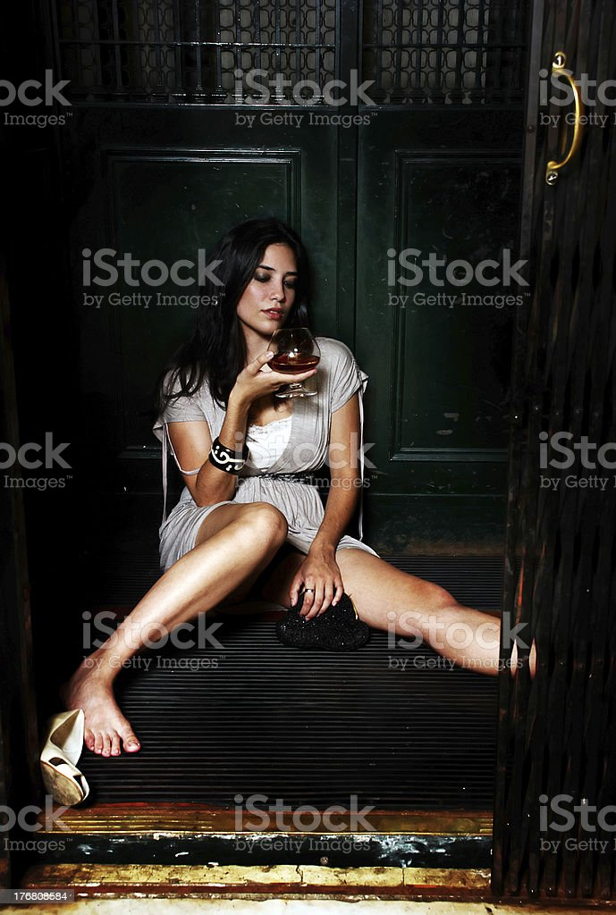 The lonely young girl with a cognac glass stock photo