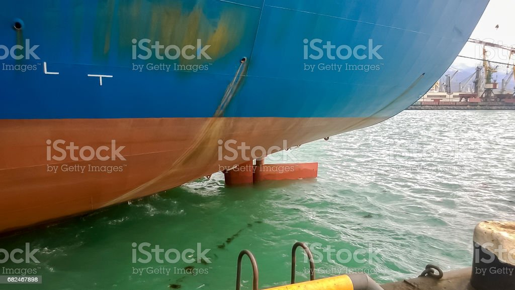 The lower part of the ship near the water. The ship is on the quay in the port stock photo