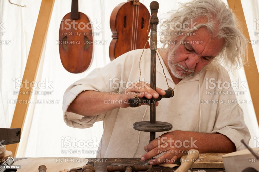 The luthier builds a medieval stringed instrument stock photo