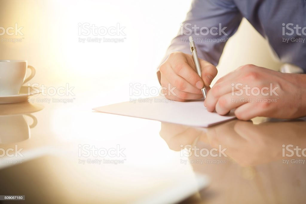 The male hands with a pen and the cup stock photo