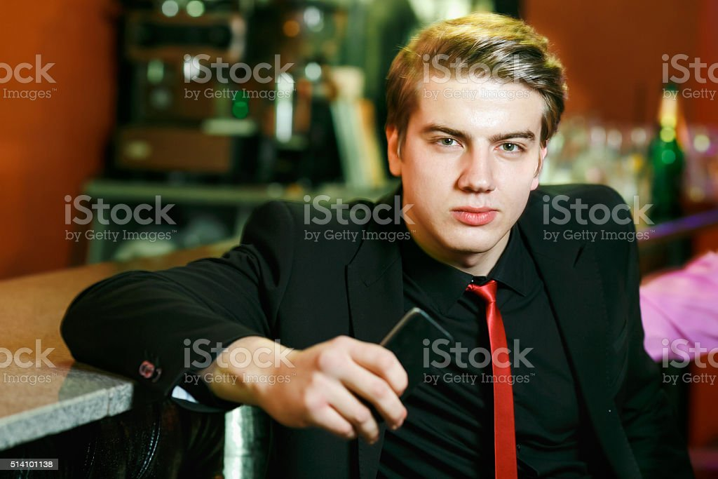 The man at the bar with a phone in his stock photo