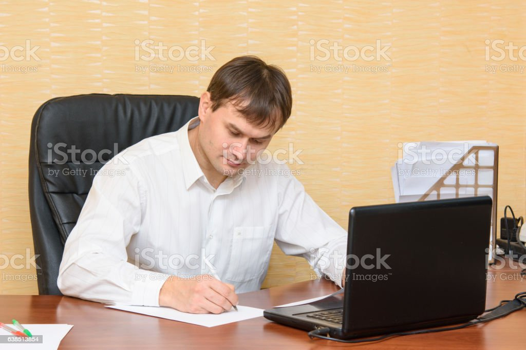 The man at the office of the table writing on paper stock photo