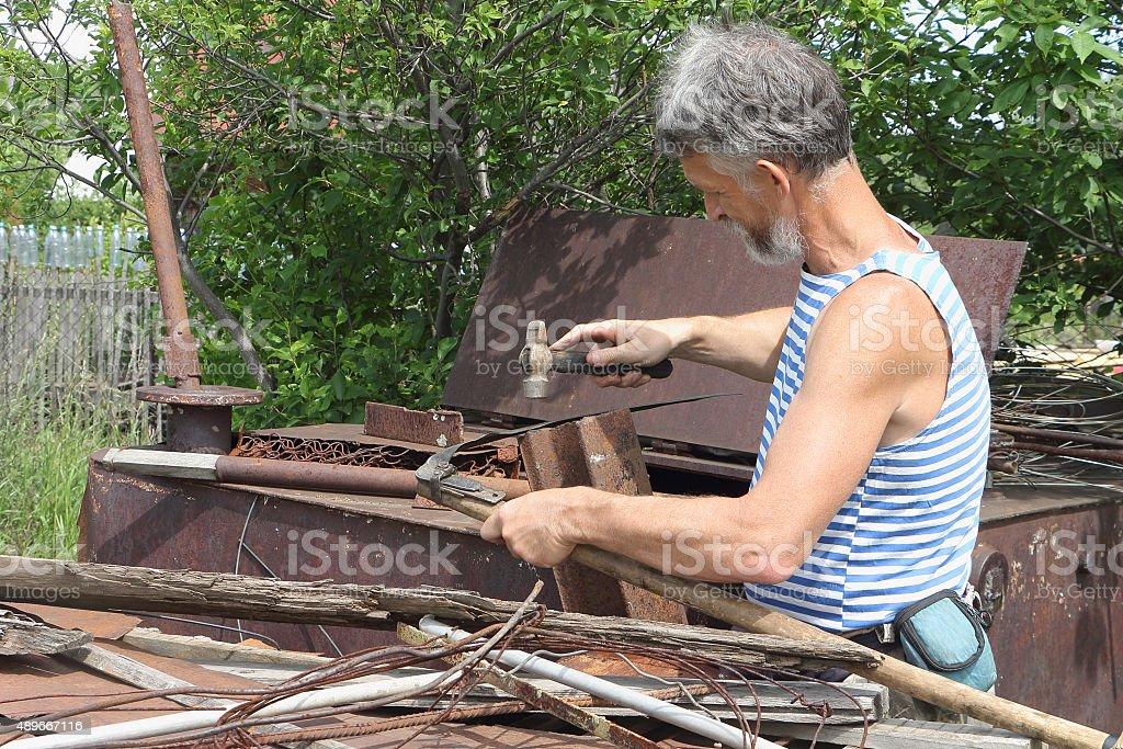 The man beats off scythe a hammer in a garden stock photo