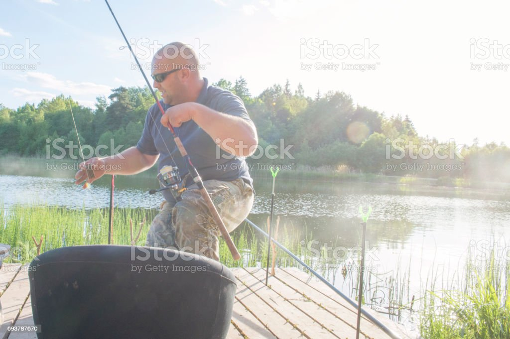The man catches fish on the river bank. stock photo