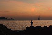 The man fishing on the rock sunset beach