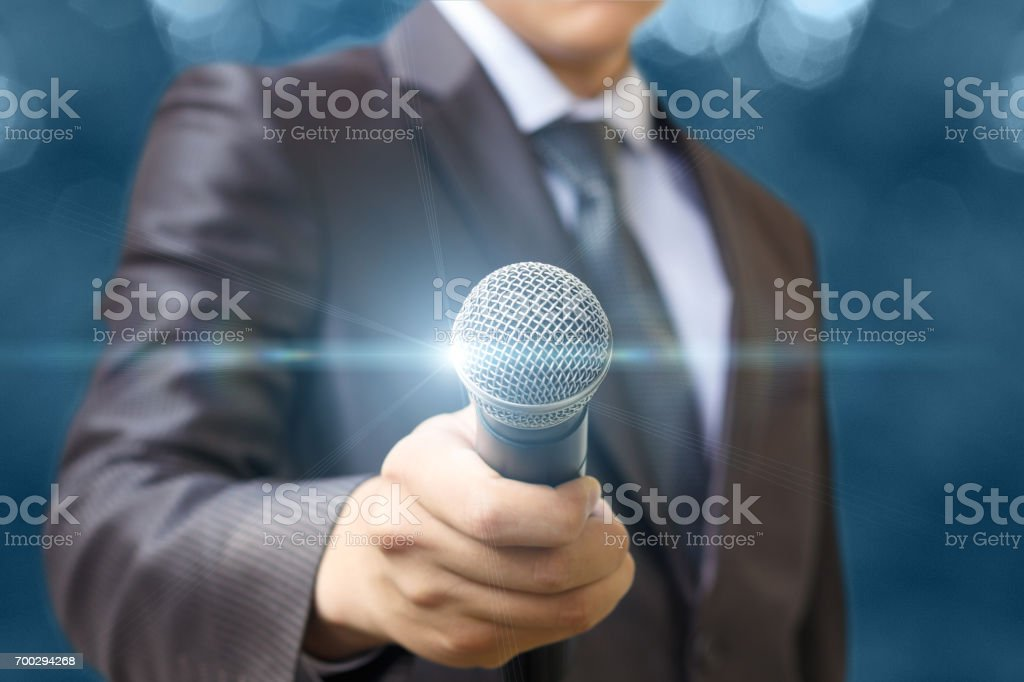 The man holds out a microphone . stock photo