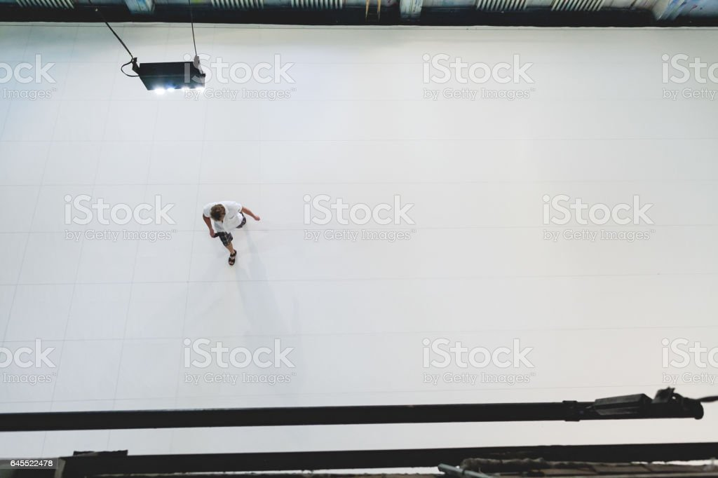 the man in a white shirt crosses the room with a white floor. top view. conceptual background stock photo