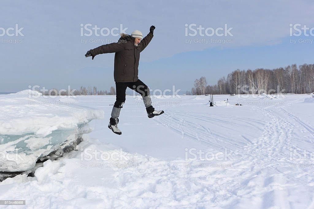 The man jumping from  of ice in the snow stock photo