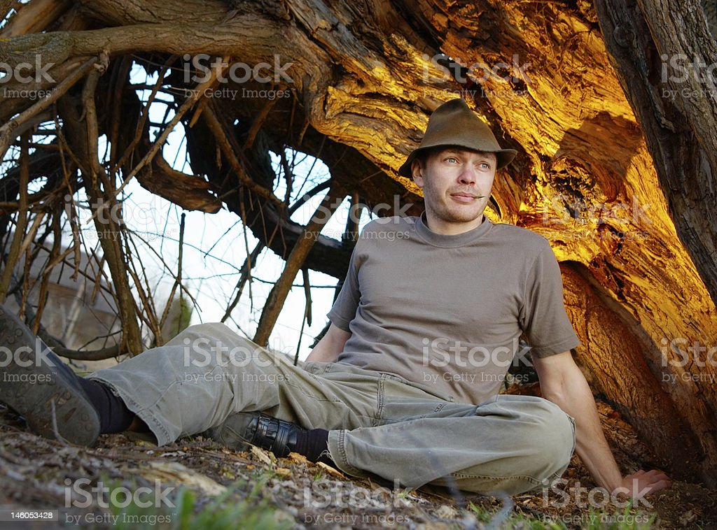The man lays under an old tree stock photo