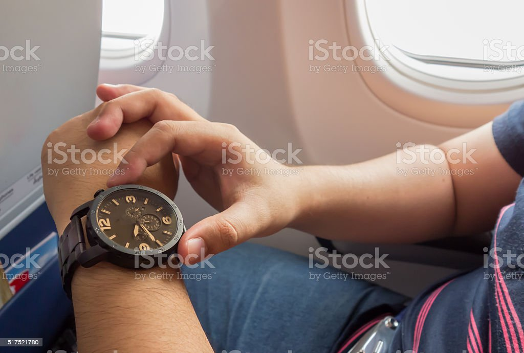 The man looking to the watch on the airplane stock photo
