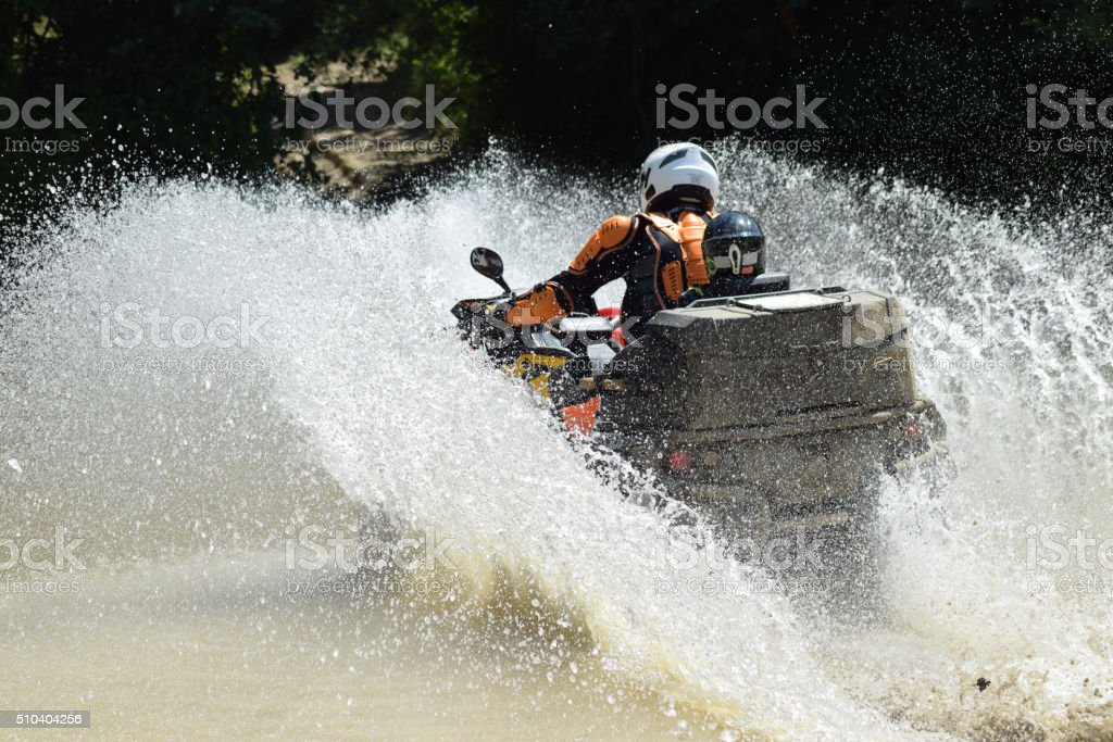 The man on the ATV crosses a stream stock photo