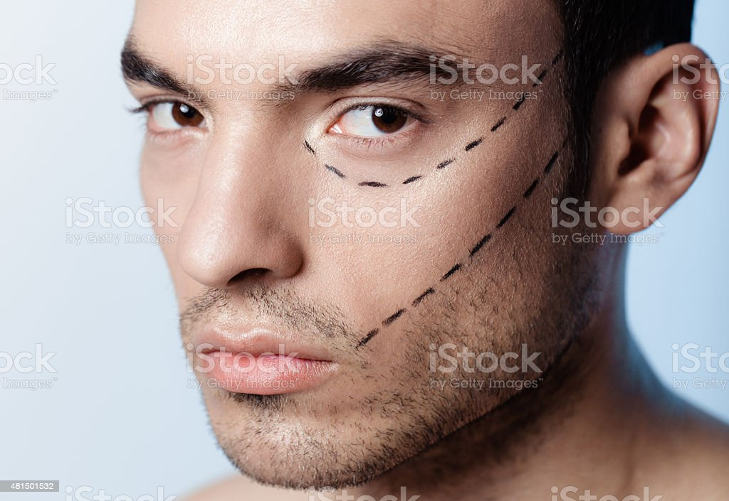 The man on the face is marked with guides stock photo