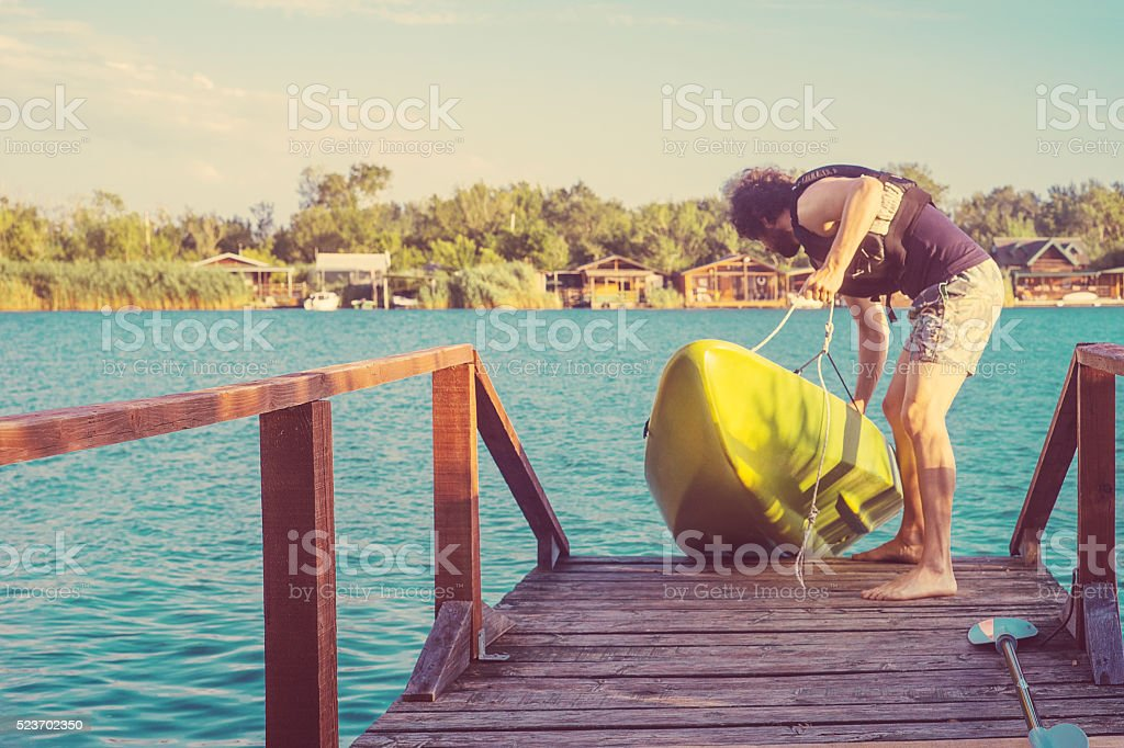 The man putting kayak into the water stock photo