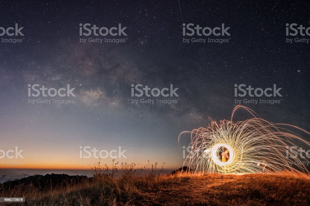 The man  rotating light  on the background of bright stars of the night sky. The Milky Way. stock photo