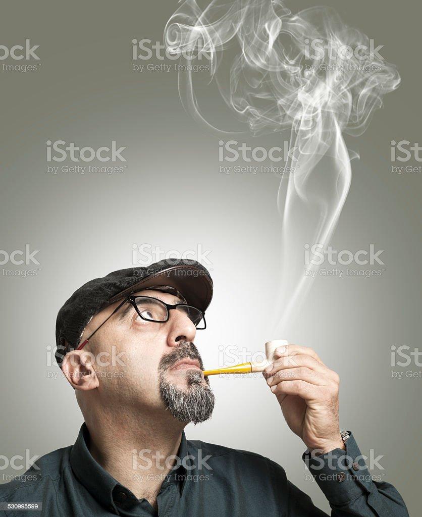 The man smokes a pipe stock photo