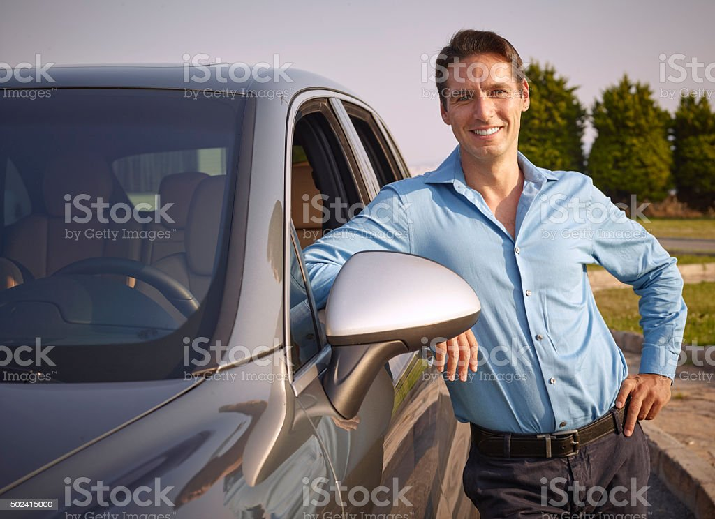 The man standing next to the car stock photo