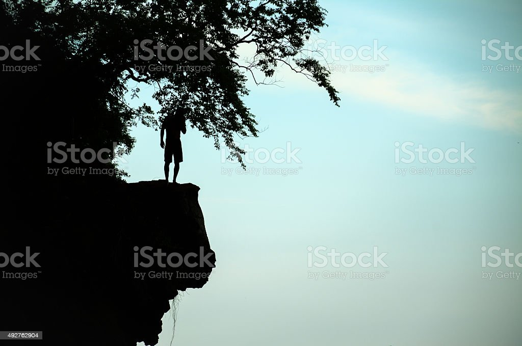 The man thinking something before cliff jump stock photo