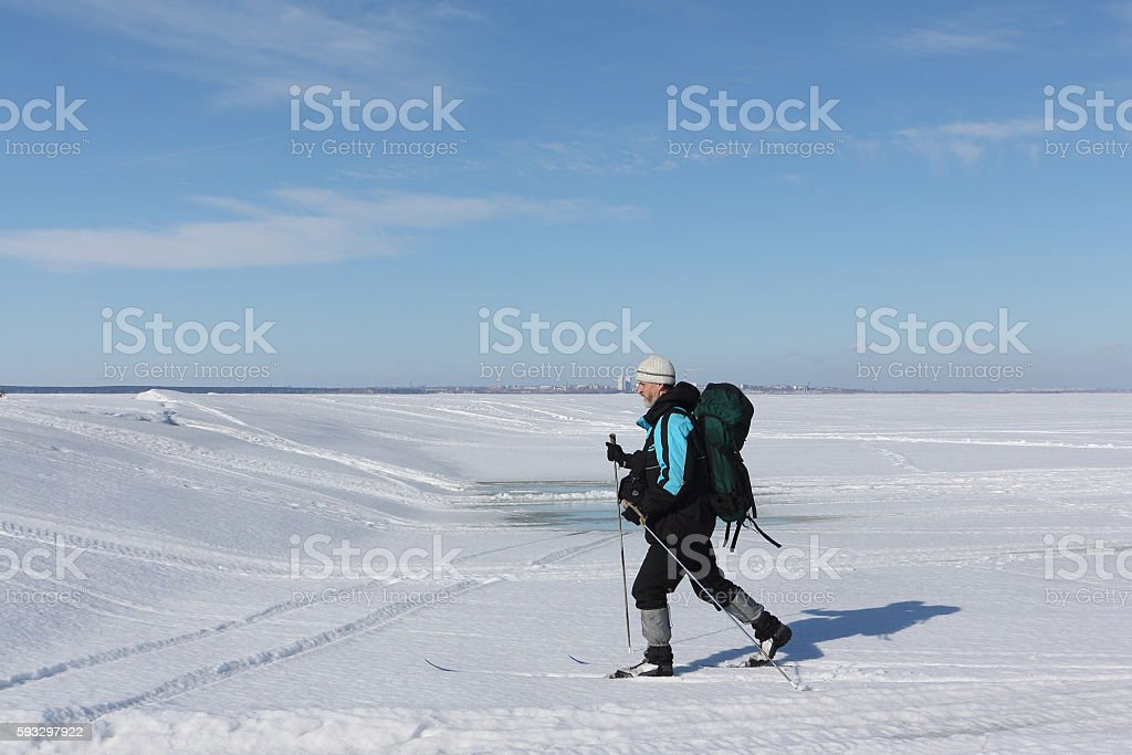 The man  with a backpack skiing on  the frozen river stock photo