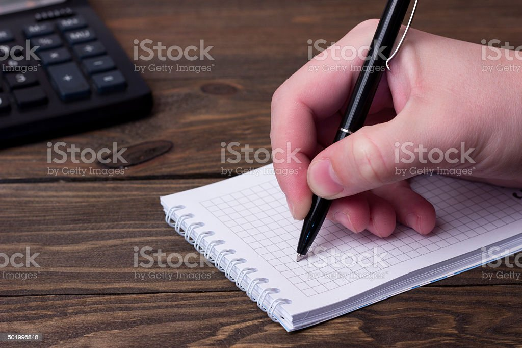 the man's hand writing with a ballpoint pen stock photo