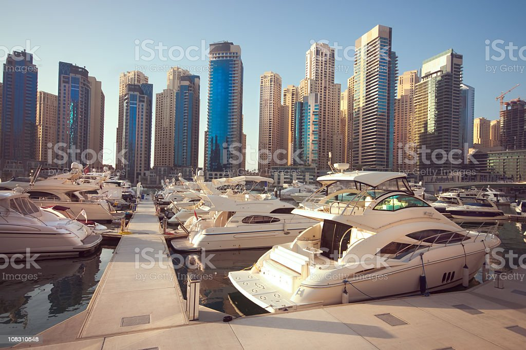 The marina in Dubai with white boats over tall buildings royalty-free stock photo