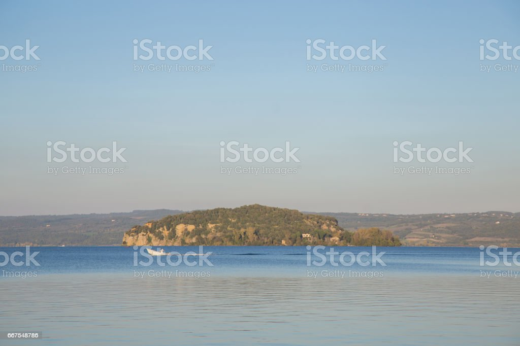 The Martana Island on Lake Bolsena with a passing fisherman with his boat. The Lake Bolsena is the largest volcanic lake in Europe. stock photo