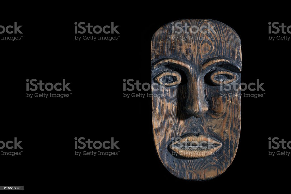 the mask is made of wood isolated on black background stock photo