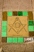 The Masonic Square and Compass are embedded in the sidewalk