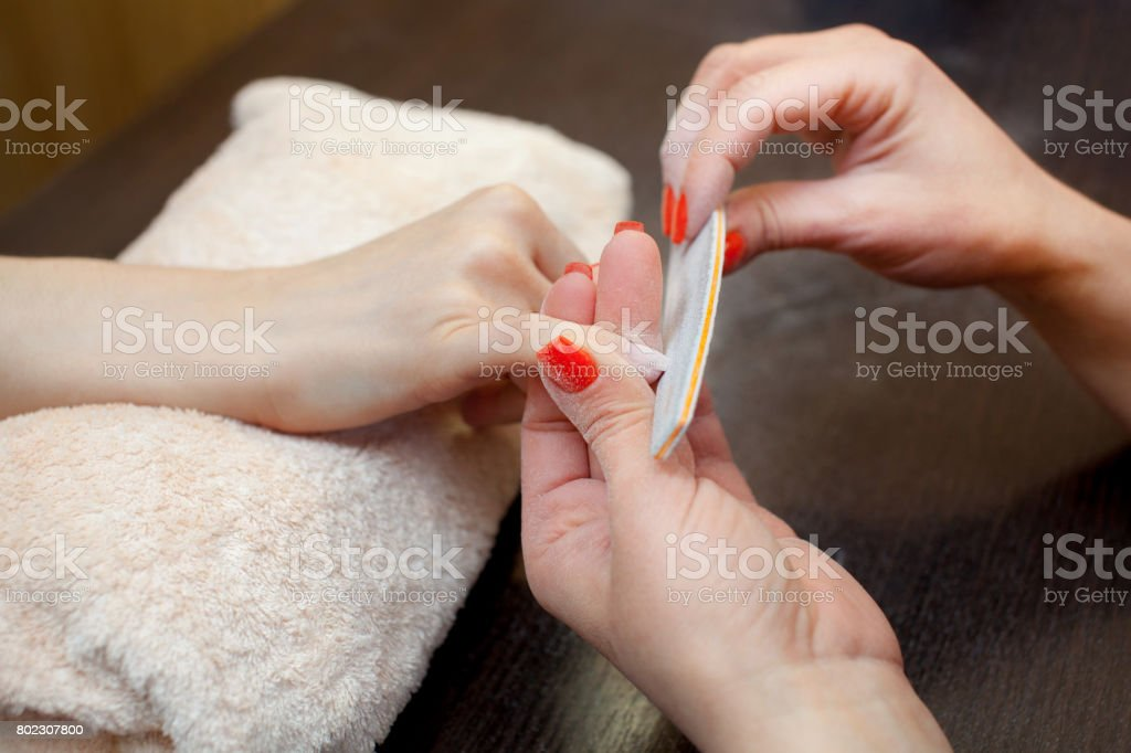 The master of the manicure saws and attaches a nail shape during the procedure of nail extensions with gel in the beauty salon. stock photo