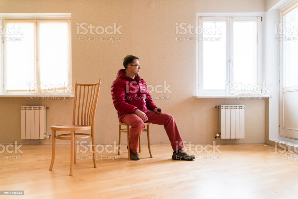 The mature man wearing red sitting on the chair in the empty living room. Full body portrait stock photo