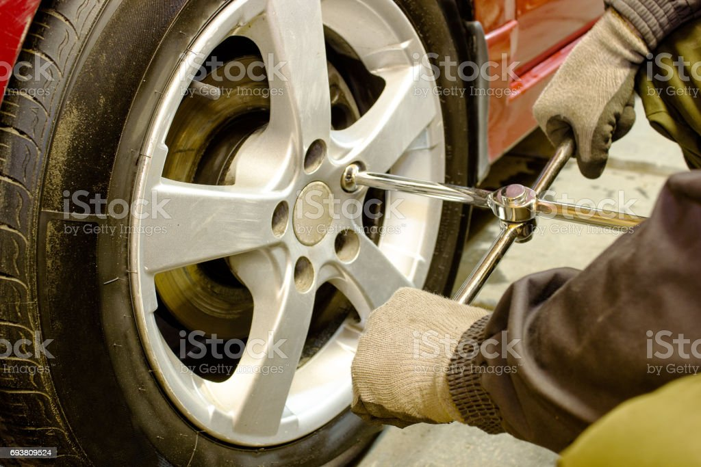 the mechanic unscrews the wheel wrench stock photo